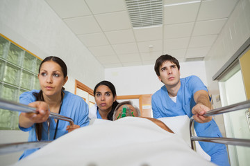 Medical team wheeling the bed of a patient in a hallway