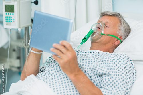 Senior patient lying on a bed with a mask while holding a tactile tablet