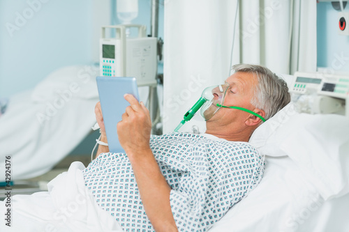 Male patient wearing an oxygen mask while holding a tactile tablet