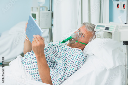 Senior patient holding a tactile tablet in his hands while wearing an oxygen mask