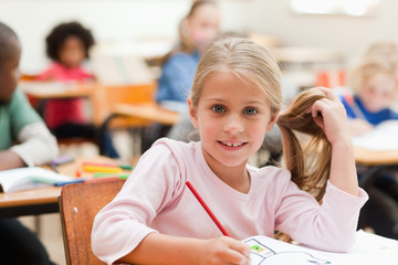 Smiling girl sitting at desk in classroom