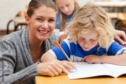Smiling teacher helping one of her students