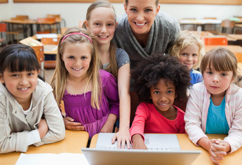 Smiling teacher with students and laptop