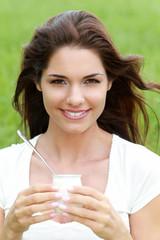 Jeune femme mangeant un yaourt dans un champ