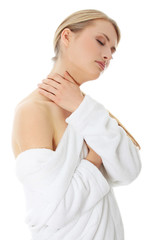 Woman wearing bathrobe is touching her naked neck.