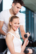 Woman Lifting Weights with Personal Trainer