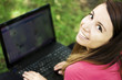 Young happy woman with laptop in a park