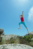 Fitness girl jumping over boulders