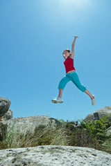 Fitness girl jumping over rocks with arms wide open