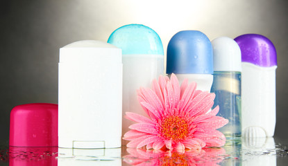 deodorant botttles with flower on grey background