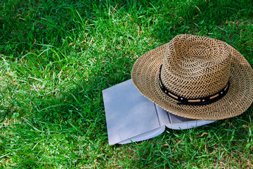Book and straw hat on grass
