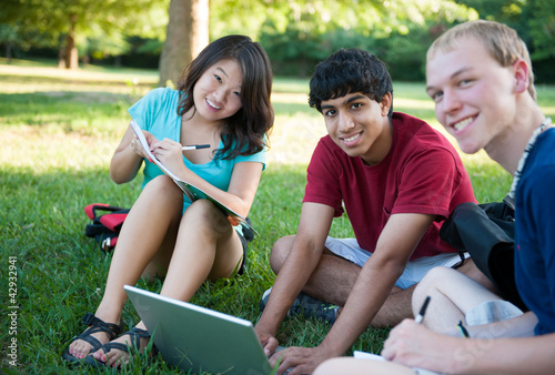 Group of three happy teenagers studying