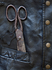 Old scissors in black leather pocket