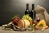 barrel, bottles and glasses of wine, cheese and ripe grapes - 42933709