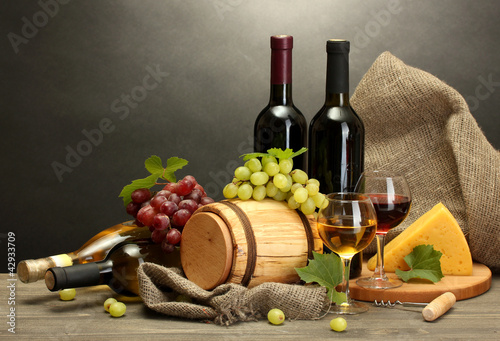 barrel, bottles and glasses of wine, cheese and ripe grapes