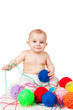 Smiling baby plays with colored balls of yarn