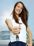 Pretty woman proudly presents the key of her car outdoors