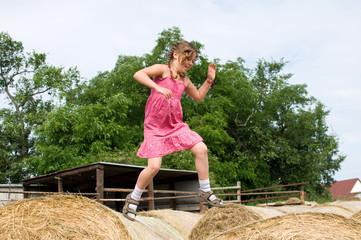 Mädchen springt über Heuballen