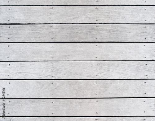 A boat dock's old, weathered and faded wood decking - 42945166