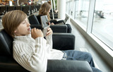 Young boy playing with a console in airport