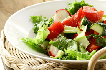 salad with tomato cucumbers and radishes dressed with olive oil