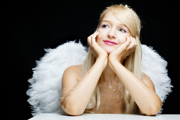 Smiling blonde angel is thinking