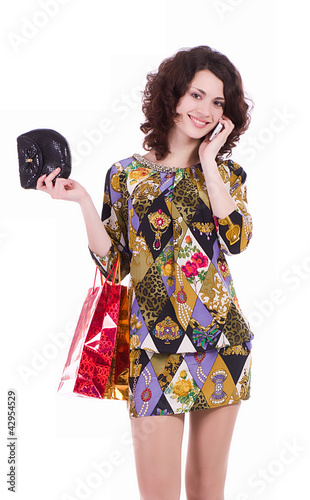 Young woman with shopping bags talking on cell phone
