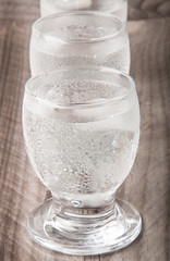 Glass of vodka  on a wooden background