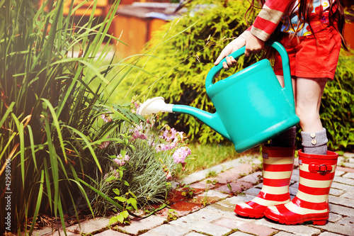 Little girl in a garden with green watering can