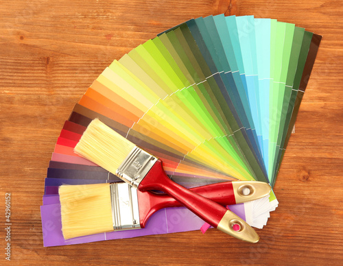 paint brushes and bright palette of colors on wooden background