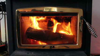 Wood stove with fire burning for heat.