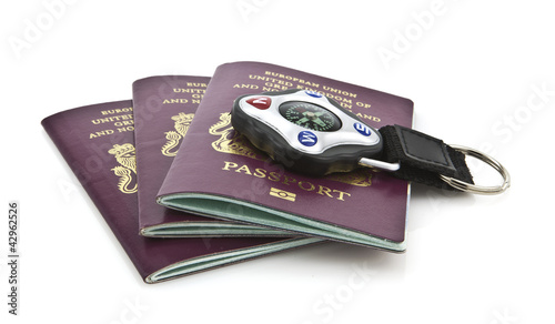 Three United Kingdom passports with compass on whithe background