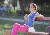 Young woman in pink trousers sitting on bench