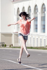 Attractive girl in shorts running along the carriageway