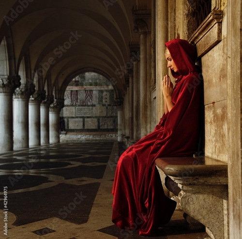 Woman in red cloak praying alone