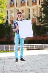 Young man smiling and holding a white cardboard