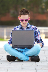 Young man smiling while typing on a notebook