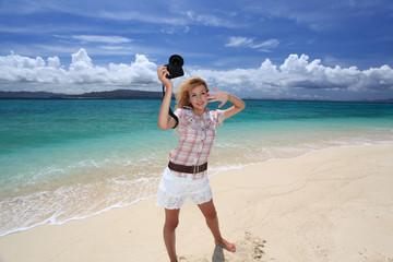 南国沖縄の海辺で撮影を楽しむ笑顔の女性