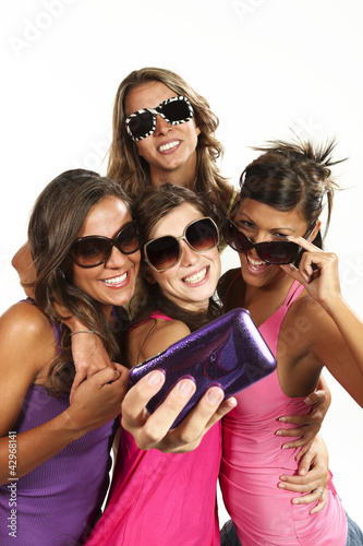 Four girls  taking pictures of themselves through cell phone