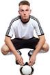 Fußballer mit Fußball und Trikot und Hose wartet auf anpfiff