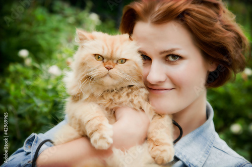 Young woman with Persian cat playing