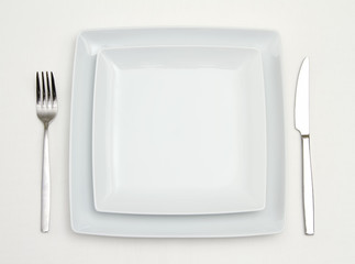 Dinner setting. white square plates with silver fork and knife