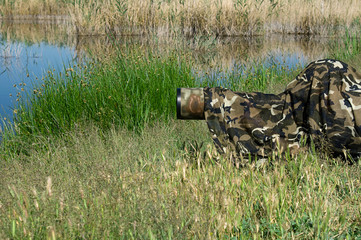 Bird photographer taking photos with camouflaged telephoto lens