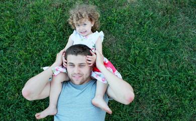 Счастливые папа и дочь лежат на траве