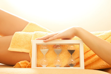 hands and legs in spa salon with a sandglass