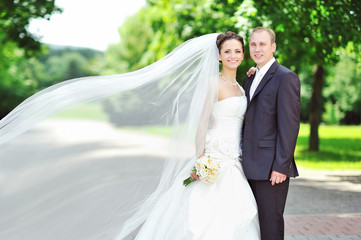 Portrait of happy bride and groom in a park