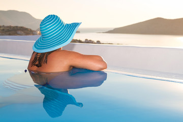 Woman in hat relaxing at swimming pool in Greece