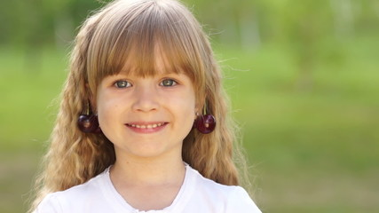 Child with cherries earrings. Closeup portrait