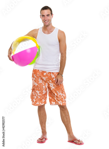 Resting on vacation smiling young man with beach ball