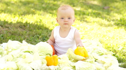 Newborn in the cabbage and vegetables outdoors